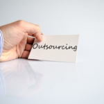 Business man hand writing Outsourcing over white background